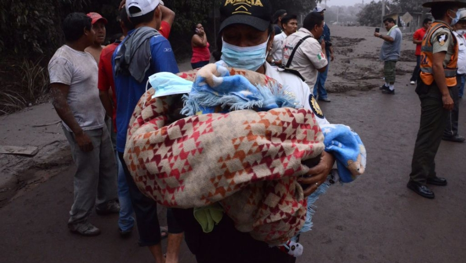 TOPSHOT - A police officer carries a baby after the eruption of the Fuego Volcano, in El Rodeo village, Escuintla department, 35 km south of Guatemala City on June 3, 2018. (Photo by NOE PEREZ / AFP) (Photo credit should read NOE PEREZ/AFP/Getty Images)