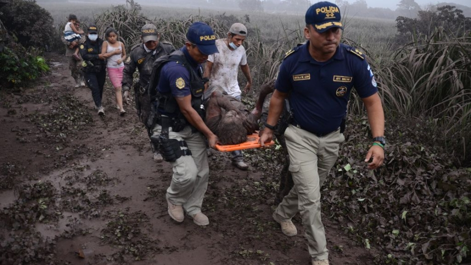 TOPSHOT - Police officers carry a wounded man after the eruption of the Fuego Volcano, in El Rodeo village, Escuintla department, 35 km south of Guatemala City on June 3, 2018. (Photo by NOE PEREZ / AFP) (Photo credit should read NOE PEREZ/AFP/Getty Images)