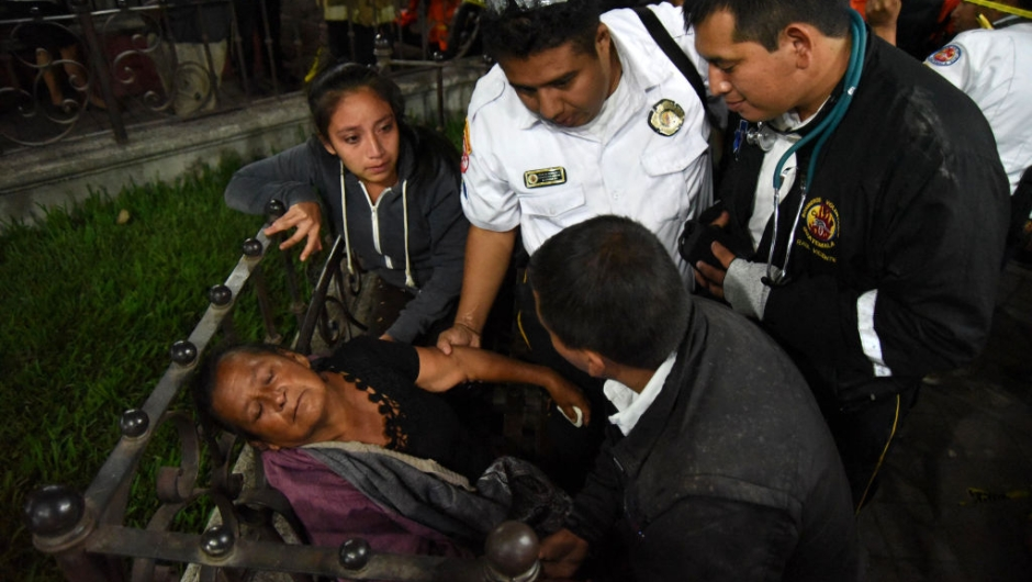 EDITORS NOTE: Graphic content / A woman is attended by firefighters after hearing a relative is among the victim's bodies at a morgue in Alotenango municipality, Sacatepequez department, about 65 km southwest of Guatemala City, after the eruption of Fuego Volcano on June 3, 2018. - At least 25 people were killed, according to the National Coordinator for Disaster Reduction (Conred), when Guatemala's Fuego volcano erupted Sunday, belching ash and rock and forcing the airport to close. (Photo by ORLANDO ESTRADA / AFP) (Photo credit should read ORLANDO ESTRADA/AFP/Getty Images)
