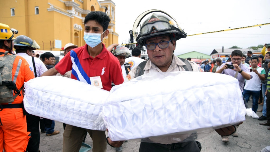 Volunteer firefighters carry to the morgue the coffins with the remais of two children, who died following the eruption of the Fuego volcano, in Alotenango municipality, Sacatepequez, about 65 km southwest of Guatemala City, on June 4, 2018. - Rescue workers Monday pulled more bodies from under the dust and rubble left by an explosive eruption of Guatemala's Fuego volcano, bringing the death toll to at least 62. (Photo by ORLANDO ESTRADA / AFP) (Photo credit should read ORLANDO ESTRADA/AFP/Getty Images)