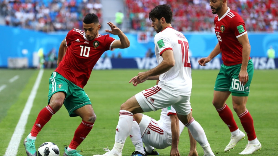 SAINT PETERSBURG, RUSSIA - JUNE 15: Younes Belhanda of Morocco is challenged by Karim Ansarifard of Iran during the 2018 FIFA World Cup Russia group B match between Morocco and Iran at Saint Petersburg Stadium on June 15, 2018 in Saint Petersburg, Russia. (Photo by