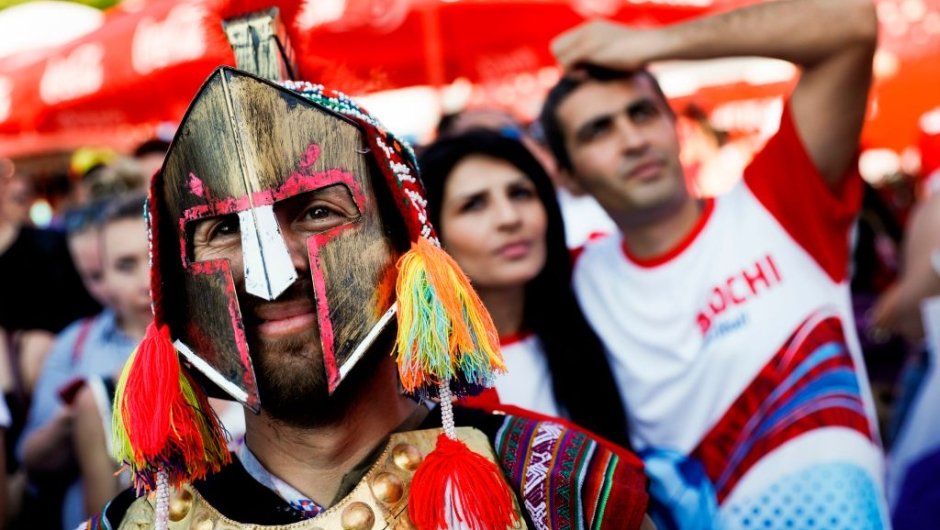 A Peruvian fan (L) stand in front of Russian football fans in the FIFA fan zone in Sochi on June 25, 2018, watching the Russia 2018 FIFA football World Cup group A match between Uruguay and Russia on a big screen. (Photo by Adrian DENNIS / AFP) (Photo credit should read ADRIAN DENNIS/AFP/Getty Images)