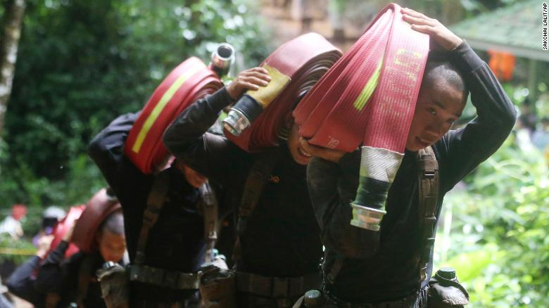 Los soldados tailandeses llevan mangueras y bombas de agua adicionales durante la búsqueda del equipo de fútbol.