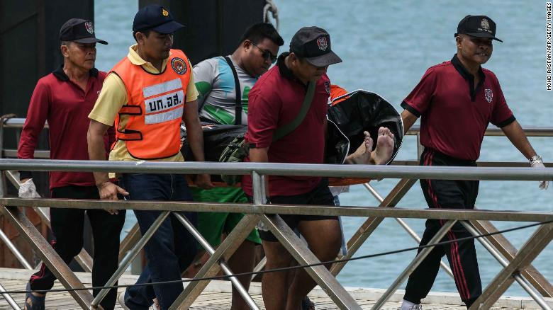 Thai rescue personnel carry a body bag bearing the recovered body of a passenger from a capsized tourist boat at Chalong pier in Phuket on July 6, 2018. - Dozens of passengers are missing after a boat capsized as high winds whipped up rough seas off the Thai tourist island of Phuket, officials said late July 5. (Photo by Mohd RASFAN / AFP) (Photo credit should read MOHD RASFAN/AFP/Getty Images)