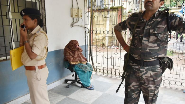 Una monja india (centro) de las Misioneras de la Caridad de la Madre Teresa esconde su rostro mientras se sienta bajo protección policial antes de una audiencia sobre cargos de tráfico de niños en Ranchi, en el estado indio de Jharkhand, el 5 de julio de 2018.