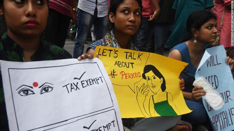 Estudiantes indios sostienen carteles y toallas sanitarias durante una protesta por impuestos en Kolkata en junio de 2017.
