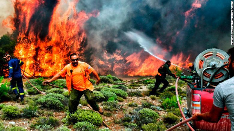 Bomberos y voluntarios trabajan para extinguir las llamas de un incendio el 24 de julio.