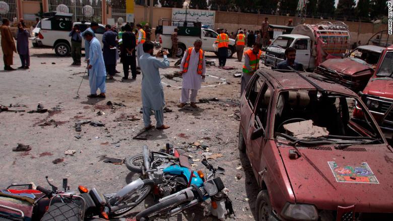 Voluntarios y agentes de seguridad paquistaníes visitan el sitio de la bomba en Quetta. (Crédito: AP Photo/Arshad Butt)