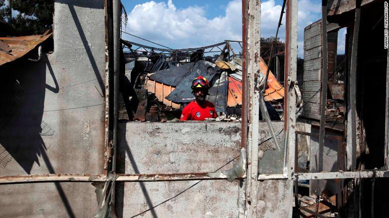 Un miembro de un equipo de rescate busca en una casa quemada en Mati el miércoles. (Crédito: AP Photo/Thanassis Stavrakis)