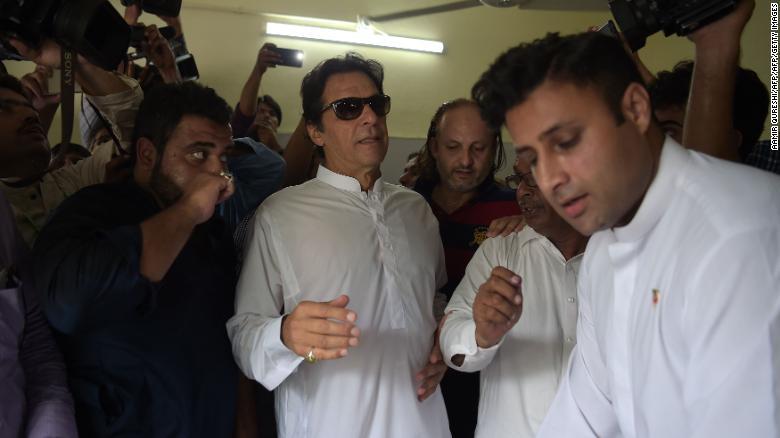 El jugador de críquet paquistaní convertido en político, Imran Khan, llega a una mesa de votación para emitir su voto.