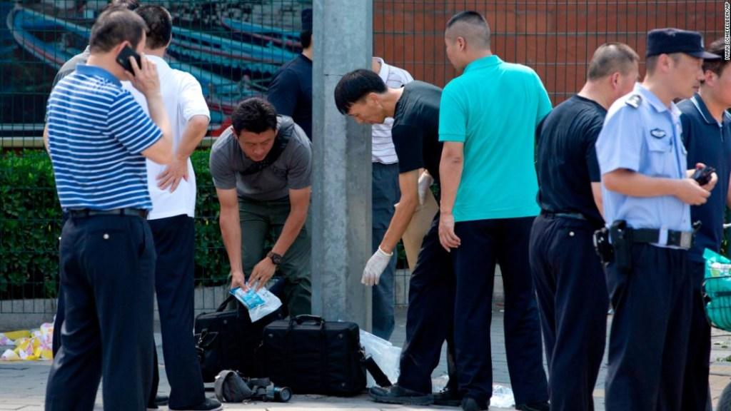 Agentes de seguridad inspeccionan el área tras una explosión cerca de la embajada de Estados Unidos en Beijing, China.