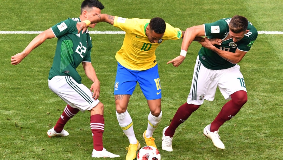 Brazil's forward Neymar (C) is marked by Mexico's forward Hirving Lozano (L) and Mexico's midfielder Hector Herrera during the Russia 2018 World Cup round of 16 football match between Brazil and Mexico at the Samara Arena in Samara on July 2, 2018. (Photo by SAEED KHAN / AFP) / RESTRICTED TO EDITORIAL USE - NO MOBILE PUSH ALERTS/DOWNLOADS (Photo credit should read SAEED KHAN/AFP/Getty Images)