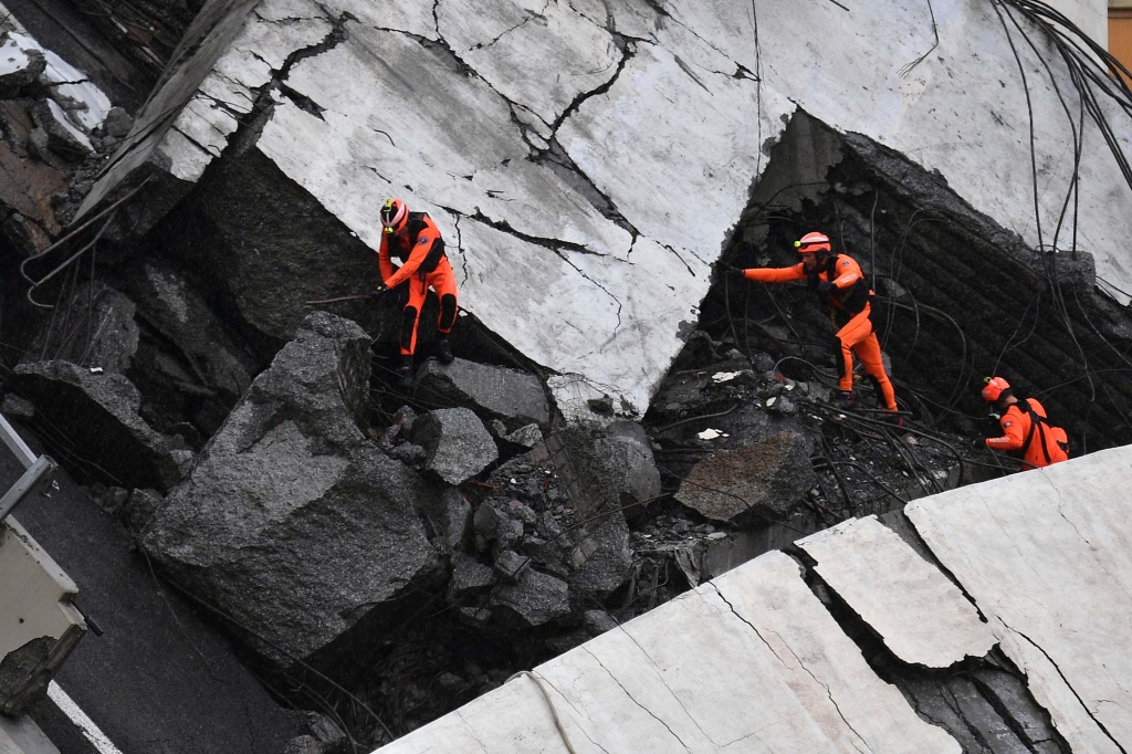 epa06948887 Rescuers at work amid the rubble after a highway bridge collapsed in Genoa, Italy, 14 August 2018. A large section of the Morandi viaduct upon which the A10 motorway runs collapsed in Genoa on Tuesday. Several people have died, rescue sources said. Several vehicles were crushed under the rubble with dead people inside, the sources said. EPA-EFE/LUCA ZENNARO