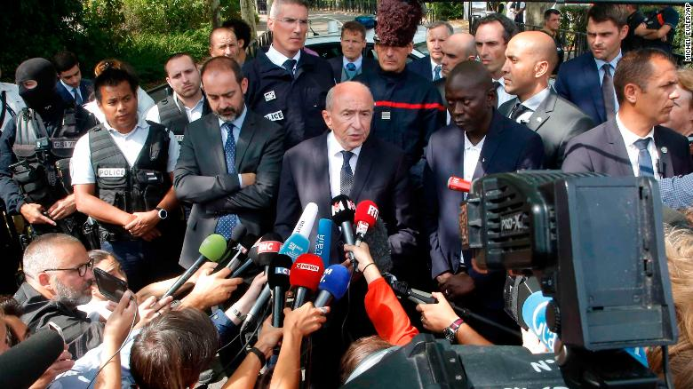 French Interior Minister Gerard Collomb, center, answers reporters after a knife attack Thursday, Aug. 23, 2018 in Trappes, west of Paris. A man flagged by French authorities as a suspected radical killed his mother and sister and seriously injured another woman in a knife attack Thursday that was quickly claimed by the Islamic State group. (AP Photo/Michel Euler)