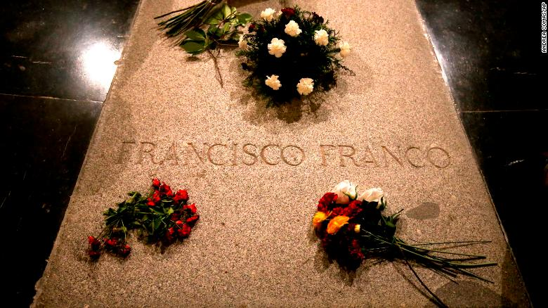 Flower are placed on the tomb of former Spanish dictator Francisco Franco inside the basilica at the the Valley of the Fallen monument near El Escorial, outside Madrid, Friday, Aug. 24, 2018. Spain's center-left government has approved legal amendments that it says will ensure the remains of former dictator Gen. Francisco Franco can soon be dug up and removed from a controversial mausoleum. (AP Photo/Andrea Comas)