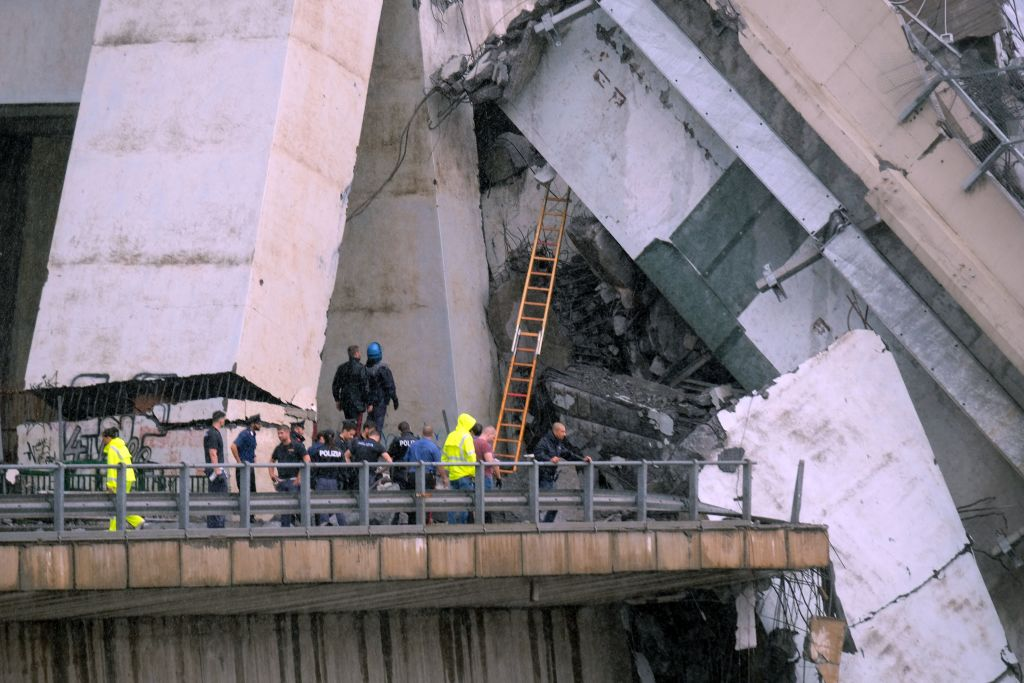 """Rescuers are at work amid the rubble of a section of a giant motorway bridge that collapsed earlier, on August 14, 2018 in Genoa. - Rescuers scouring through the wreckage after part of a viaduct of the A10 freeway collapsed said there were """"tens of victims"""", while images from the scene showed an entire carriageway plunged on to railway lines below. (Photo by ANDREA LEONI / AFP) (Photo credit should read ANDREA LEONI/AFP/Getty Images)"""
