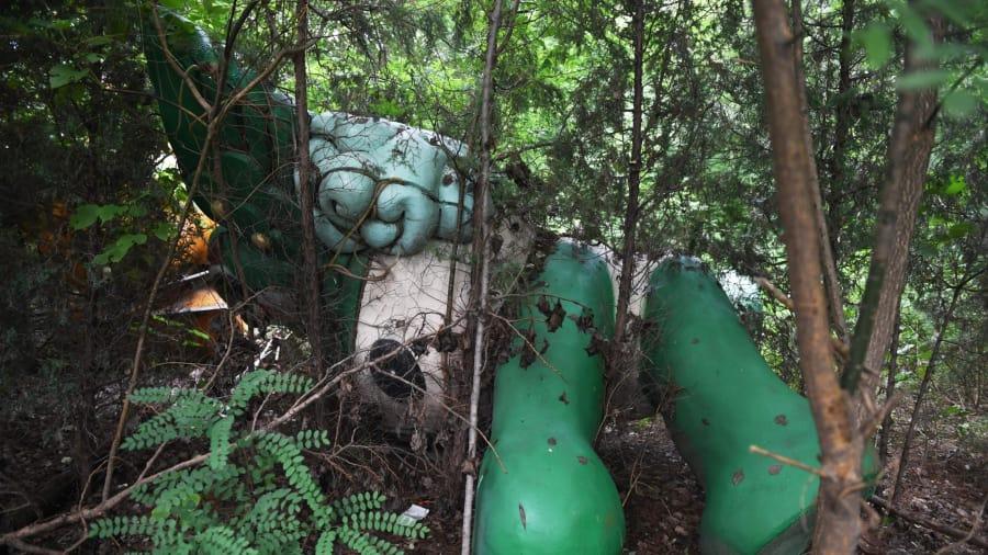 Reclamado por naturaleza: Nini, otra de las mascotas de los Juegos, se ve entre árboles detrás del centro comercial abandonado y nunca terminado en Beijing.
