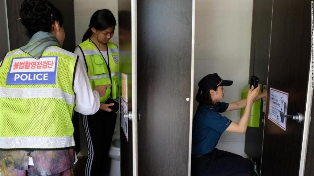 Un escuadrón de búsqueda de cámara oculta, formado por voluntarios estudiantes y ciudadanos, escanea un baño cerca de una piscina pública en Changwon, Corea del Sur, el 25 de julio de 2018.