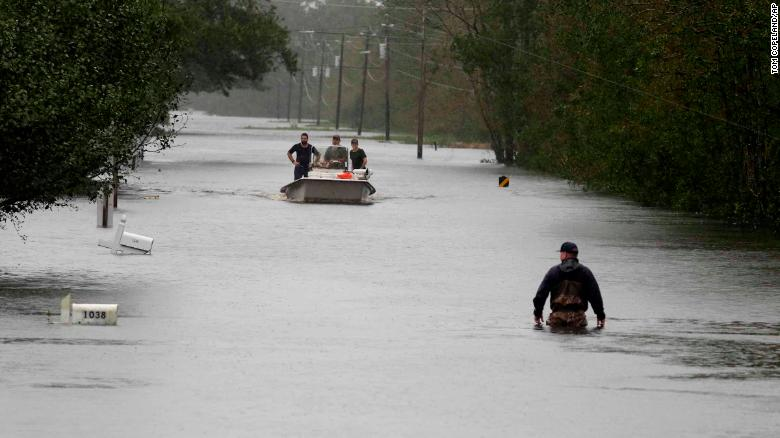 A member of the U.S. Coast Guard walks down Mill Creek Road checking houses after tropical storm Florence hit Newport N.C., Saturday, Sept. 15, 2018. (AP Photo/Tom Copeland)