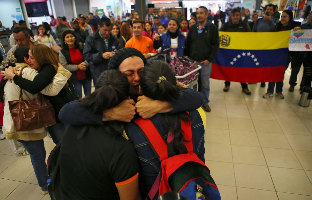 """Venezuelan migrants are embraced by relatives upon their arrival at the bus terminal in the north of Lima, after traveling for 20 hours from Tumbes, northwestern Peru, on August 26, 2018. - Venezuelan migrants denounced on Saturday that Ecuador """"cheated"""" on them and delayed their transfer by road to Peru, which prevented them from crossing to that country before the passport requirement began to apply. (Photo by Teo BIZCA / AFP) (Photo credit should read TEO BIZCA/AFP/Getty Images)"""