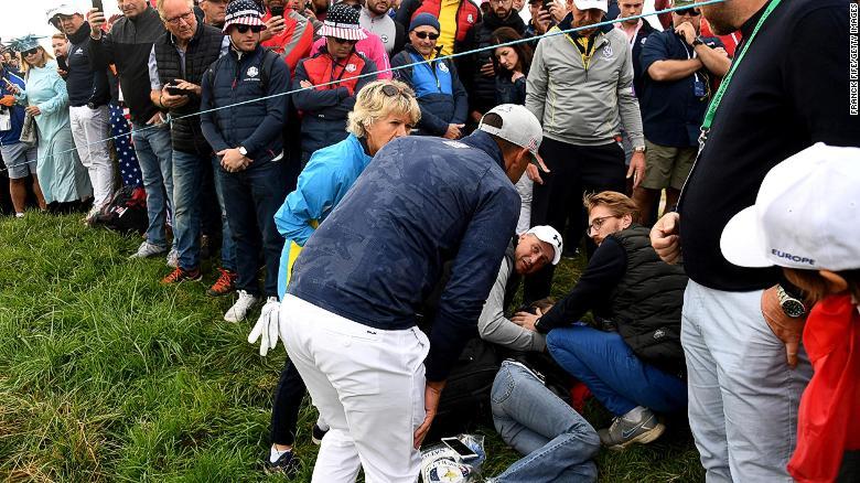 El golfista estadounidense Brooks Koepka asiste a un espectador lesionado en la Ryder Cup cerca de París.