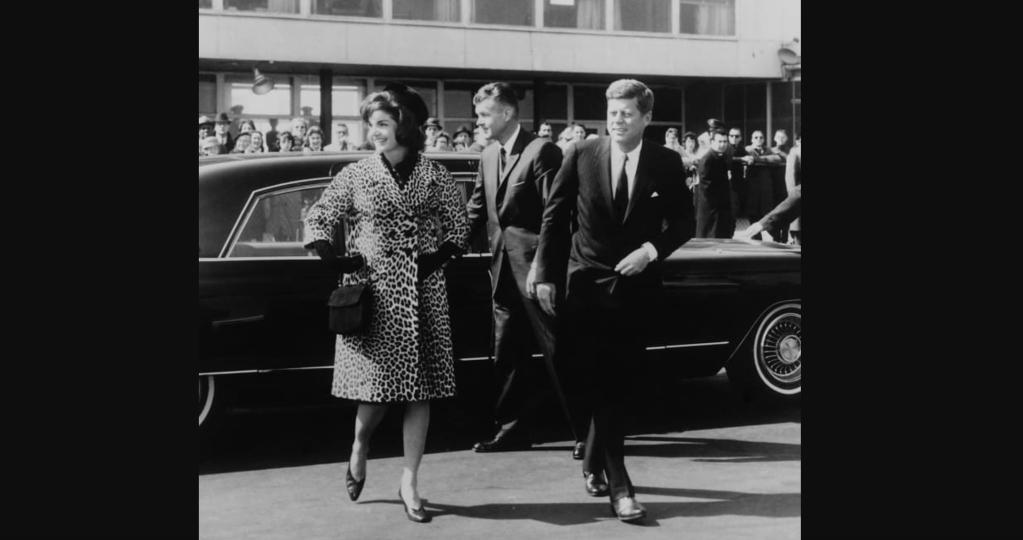 Escoltada por el presidente Kennedy, Jacqueline Kennedy sale para un viaje a India y Pakistán con un abrigo de piel de leopardo Oleg Cassini en 1962. (Crédito: Cortesía de la colección Everett)