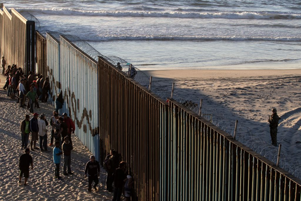 """TOPSHOT - Central American migrants moving towards the United States in hopes of a better life, stand by the US-Mexico border fence in Playas de Tijuana, Mexico, on November 14, 2018. - US Defence Secretary Jim Mattis said Tuesday he will visit the US-Mexico border, where thousands of active-duty soldiers have been deployed to help border police prepare for the arrival of a """"caravan"""" of migrants. (Photo by Guillermo Arias / AFP) (Photo credit should read GUILLERMO ARIAS/AFP/Getty Images)"""