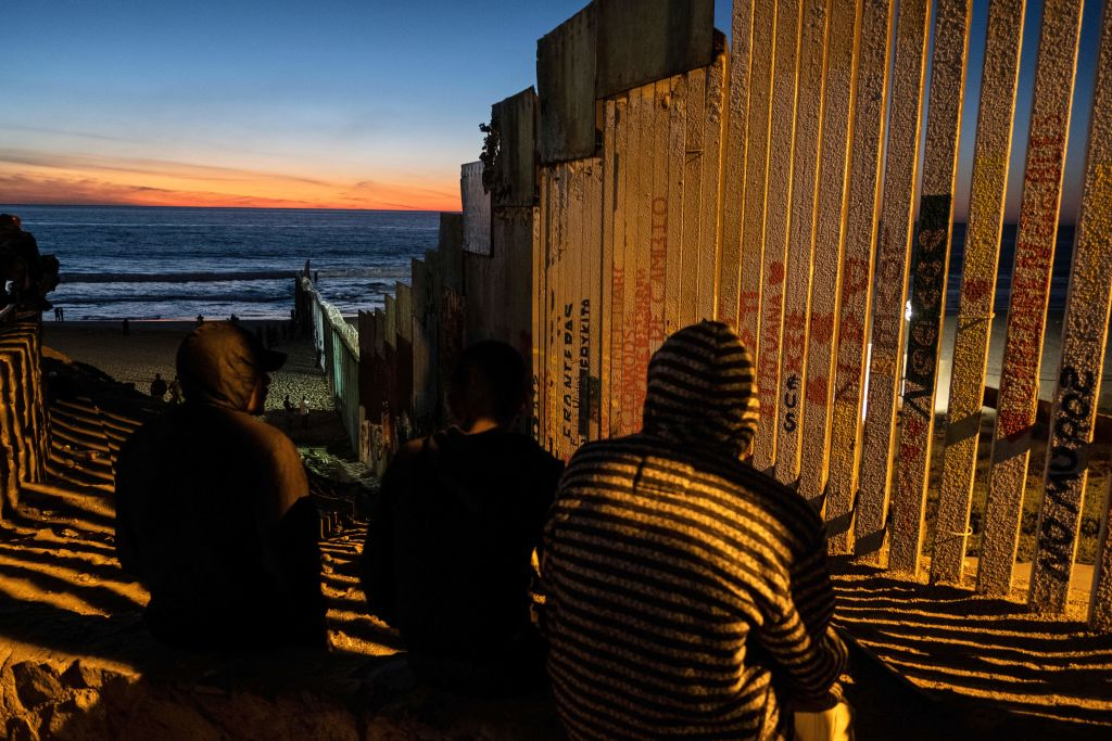 """TOPSHOT - Central American migrants moving towards the United States in hopes of a better life, are seen near the US-Mexico border fence in Playas de Tijuana, Mexico, on November 14, 2018. - US Defence Secretary Jim Mattis said Tuesday he will visit the US-Mexico border, where thousands of active-duty soldiers have been deployed to help border police prepare for the arrival of a """"caravan"""" of migrants. (Photo by Guillermo Arias / AFP) (Photo credit should read GUILLERMO ARIAS/AFP/Getty Images)"""