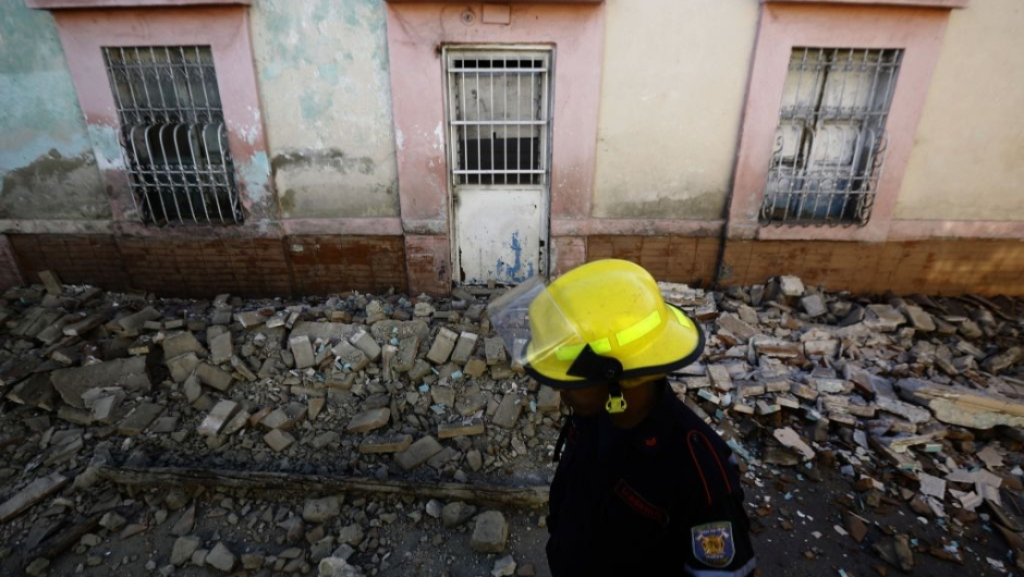 TOPSHOT - A firefighter walks in front of a house damaged during a 4.9 earthquake in Valencia, Carabobo State, Venezuela, on December 27, 2018. - A strong tremor followed by a score of aftershocks shook Caracas and several Venezuelan states early this Thursday, the Venezuelan Foundation for Seismological Research (Funvisis) reported. (Photo by JUAN CARLOS HERNANDEZ / AFP) (Photo credit should read JUAN CARLOS HERNANDEZ/AFP/Getty Images)