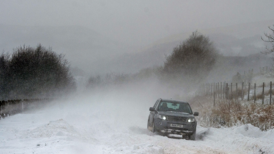 A car is driven along the A670 in snow near the village of Diggle, east of Manchester in northern England on March 18, 2018, as the wintry weather makes a return to the country. The Met Office has weather warnings in place for the UK as some areas expect up to 25cm of snow to fall on Sunday. / AFP PHOTO / Oli SCARFF (Photo credit should read OLI SCARFF/AFP/Getty Images)
