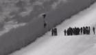 Migrantes cruzan el muro fronterizo usando una escalera