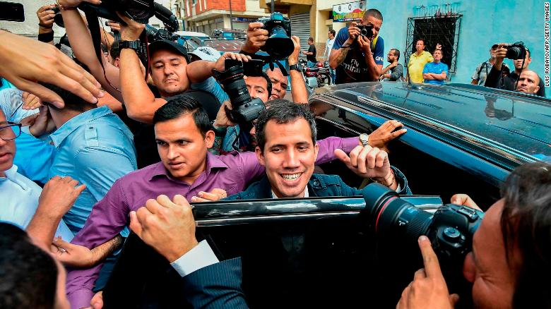 """Venezuela's National Assembly head and self-proclaimed """"acting president"""" Juan Guaido (C) leaves after attending a mass in honour to the fallen in the fight for freedom, political prisoners and the exiled, at the San Jose church in Caracas on January 27, 2019. - Guaido, who has galvanized a previously divided opposition, is offering an amnesty approved by the opposition-controlled National Assembly to anyone in the military who disavows President Nicolas Maduro, even suggesting amnesty for Maduro himself. (Photo by Luis ROBAYO / AFP) (Photo credit should read LUIS ROBAYO/AFP/Getty Images)"""