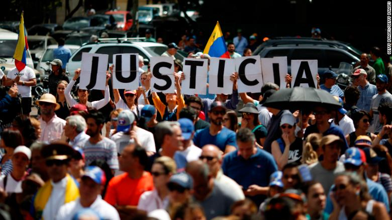 """Demonstrators hold banner that reads """"Justice"""" during a rally of the opposition with the self-proclaimed interim president Guaido in Caracas, January 25, 2018. Marco BelloDemonstrators hold banner that reads """"Justice"""" during a rally of the opposition with the self-proclaimed interim president Guaido in Caracas, January 25, 2018. Marco Bello"""