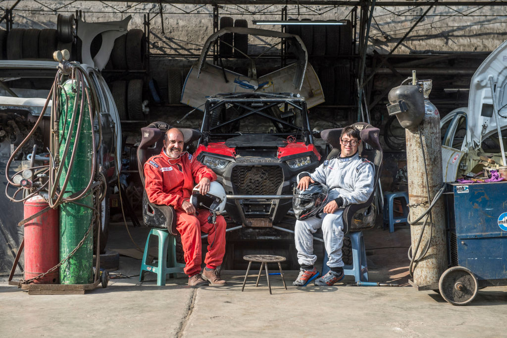 Jacques Barron (L) and his son and co-driver Lucas Barron, 25, pose at a mechanics workshop in Lima, on December 18, 2018, where their car is being prepared to take part in the upcoming Rally Dakar on January 2019. - Lucas Barron will make history on January 6 when he lines up on the Dakar 2019 start line in Peru, the first person with Down Syndrome to take part in the gruelling race. The 25-year-old, who will be co-pilot for his father Jacques, will tackle the world's most demanding rally: a 5,000 kilometer (3,000 miles), 10-day marathon, 70 percent of which will be raced over sand. (Photo by ERNESTO BENAVIDES / AFP) (Photo credit should read ERNESTO BENAVIDES/AFP/Getty Images)