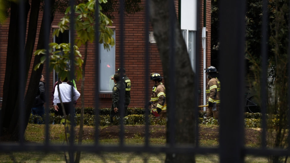 "Security forces and firefighters work at the site of an apparent car bomb attack on a police cadet training school in Bogota, that left at least four people dead and 10 injured on January 17, 2019. - ""It seems there was a car bomb inside the General Santander School,"" said the city's mayor, Enrique Penalosa. (Photo by JUAN BARRETO / AFP) (Photo credit should read JUAN BARRETO/AFP/Getty Images)"