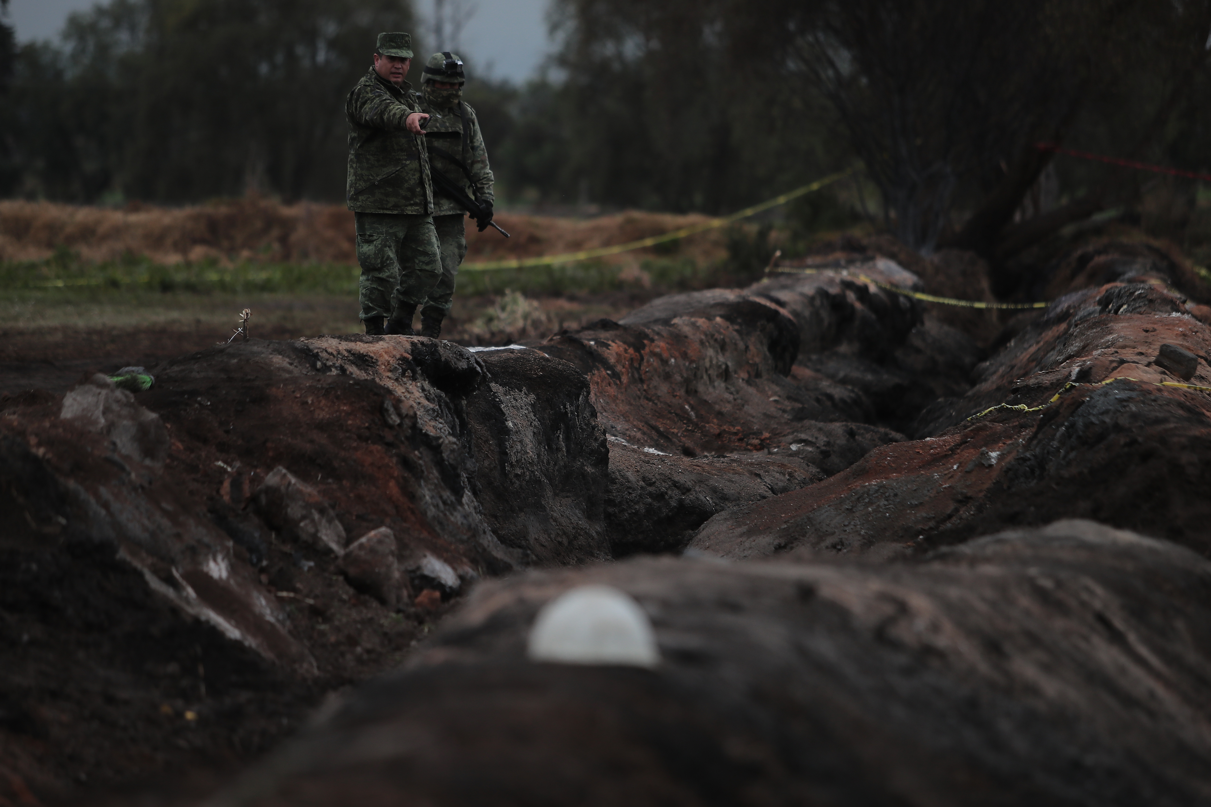 TLAHUELILPAN, MEXICO - JANUARY 20: Members of the Military watch over the explosion area of the pipeline on January 20, 2019 in Tlahuelilpan, Mexico. In a statement, PEMEX announced that the explosion was caused by the illegal manipulation of the pipeline, as minutes before the accident videos were shot where people could be seen filling drums and car fuel tanks. (Photo by Hector Vivas/Getty Images)
