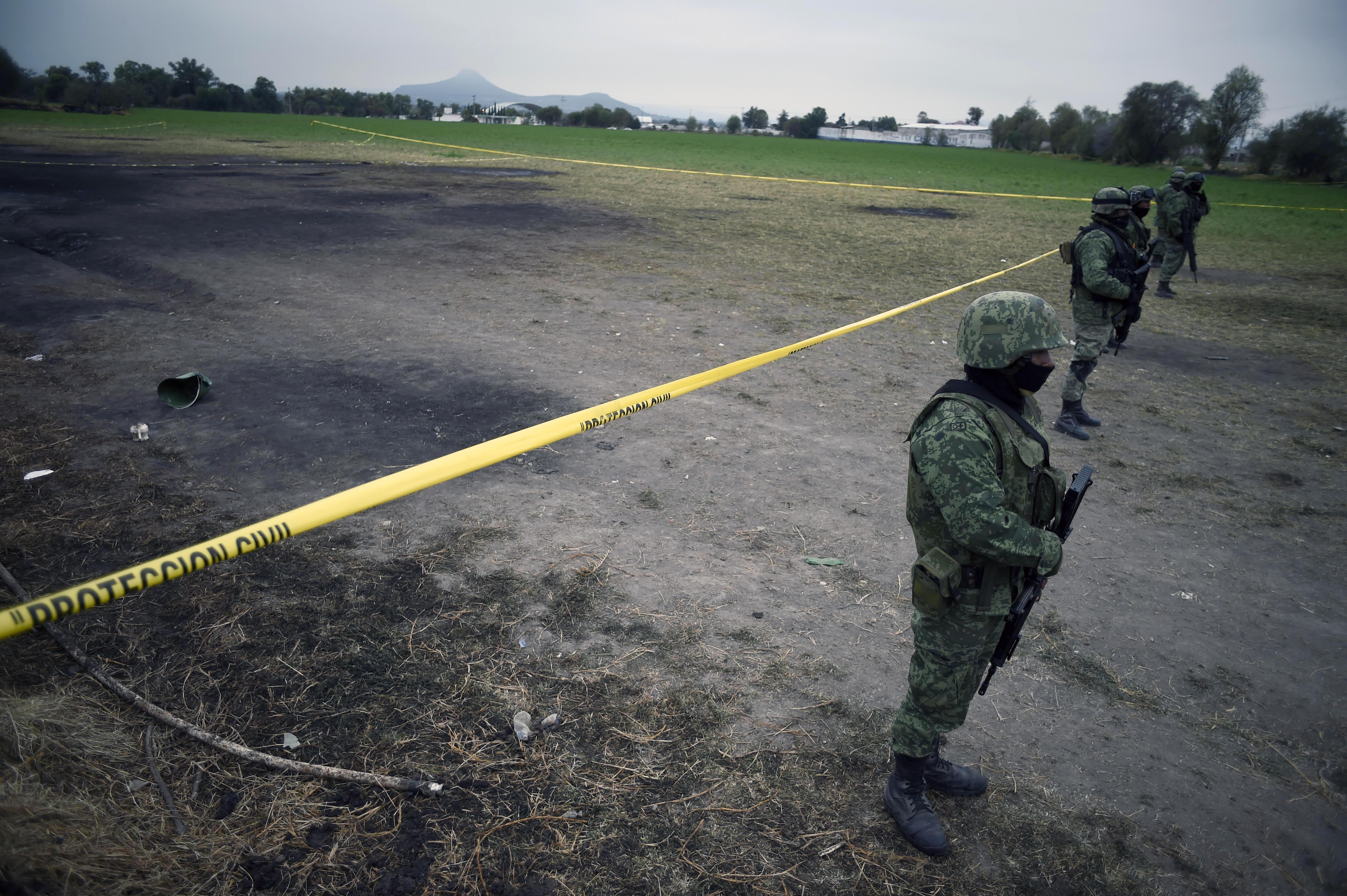Mexican soldiers stand guard at the site of a massive blaze triggered by a leaky pipeline in Tlahuelilpan, Hidalgo state, Mexico on January 20, 2019. - An explosion and fire in central Mexico killed at least 73 people after hundreds swarmed to the site of an illegal fuel-line tap to gather gasoline amid a government crackdown on fuel theft, officials said. (Photo by ALFREDO ESTRELLA / AFP) (Photo credit should read ALFREDO ESTRELLA/AFP/Getty Images)