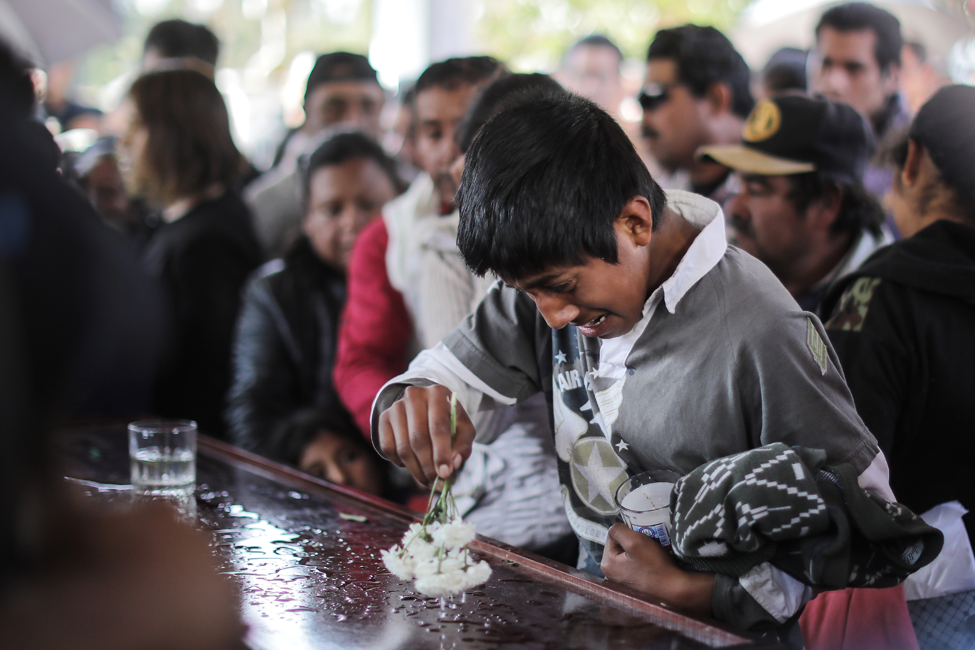 TLAHUELILPAN, MEXICO - JANUARY 20: Relatives and friends of a deceased cry before the burial in the pantheon after the funeral services of the victims of an explosion in a pipeline belonging to Mexican Public Oil Company Pemex on January 20, 2019 in Tlahuelilpan, Mexico. In a statement, PEMEX announced that the explosion was caused by the illegal manipulation of the pipeline, as minutes before the accident videos were shot where people could be seen filling drums and car fuel tanks. (Photo by Hector Vivas/Getty Images)