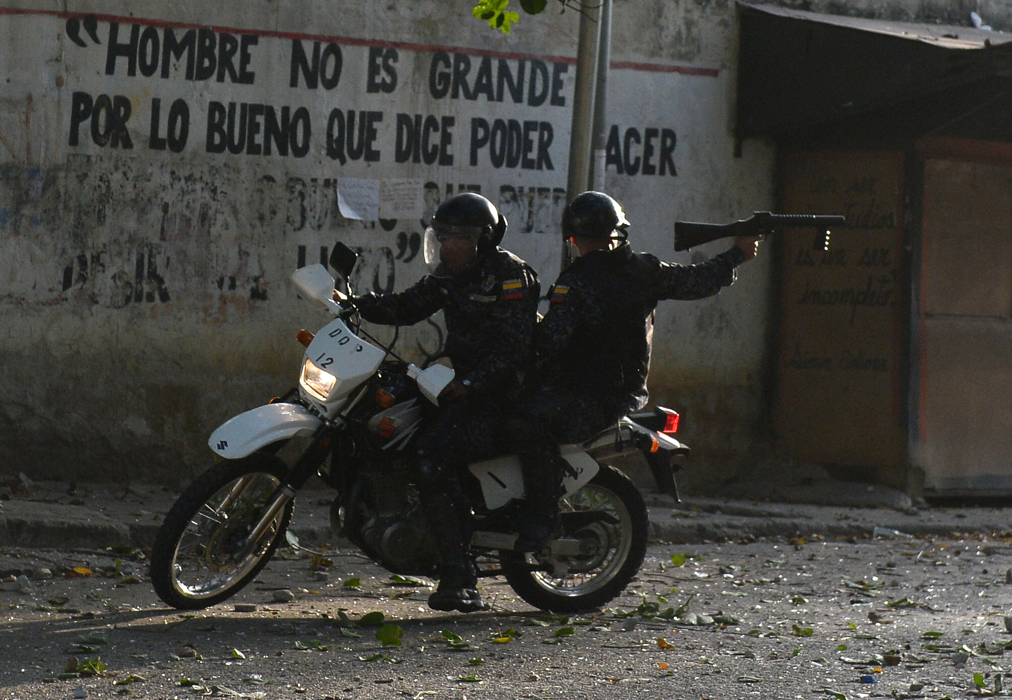 TOPSHOT - A riot policeman on a motorcycle points his gun during clashes with anti-government demonstrators in the neighborhood of Los Mecedores, in Caracas, on January 21, 2019. - A group of soldiers rose up against Venezuela's President Nicolas Maduro at a command post in northern Caracas on Monday, but were quickly arrested after posting an appeal for public support in a video, the government said. (Photo by Federico Parra / AFP) (Photo credit should read FEDERICO PARRA/AFP/Getty Images)