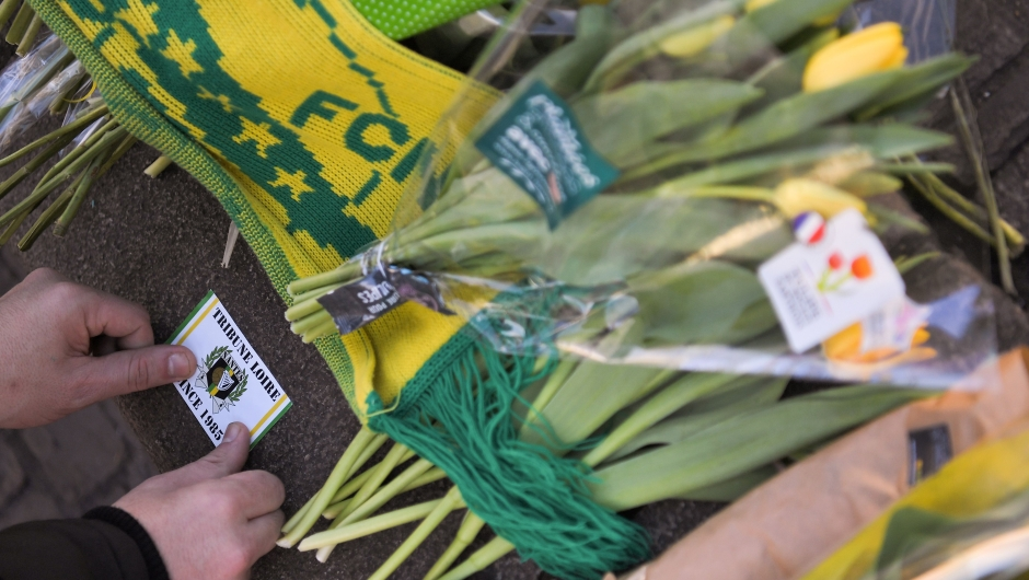 A FC Nantes football club supporter places a sticker close to flowers placed in the main square of the city of Nantes, western France, two days after it was announced that the plane carrying Argentinian forward Emiliano Sala vanished during a flight from Nantes to Cardiff in Wales, on January 23, 2019. - The 28-year-old Argentine striker is one of two people still missing after contact was lost with the light aircraft he was travelling on, on January 21, 2019 night. Sala was on his way to the Welsh capital to train with his new teammates for the first time after completing a £15 million pounds sterling ($19 million US dollars) move to Cardiff City from French side Nantes on January 19. (Photo by LOIC VENANCE / AFP) (Photo credit should read L