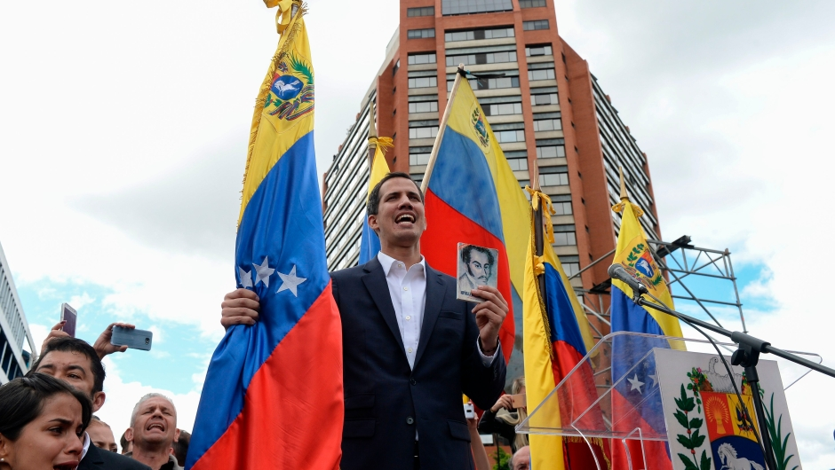 "Venezuela's National Assembly head Juan Guaido declares himself the country's ""acting president"" during a mass opposition rally against leader Nicolas Maduro, on the anniversary of a 1958 uprising that overthrew a military dictatorship, in Caracas on January 23, 2019. - Moments earlier, the loyalist-dominated Supreme Court ordered a criminal investigation of the opposition-controlled legislature. ""I swear to formally assume the national executive powers as acting president of Venezuela to end the usurpation, (install) a transitional government and hold free elections,"" said Guaido as thousands of supporters cheered. (Photo by Federico PARRA / AFP) (Photo credit should read FEDERICO PARRA/AFP/Getty Images)"
