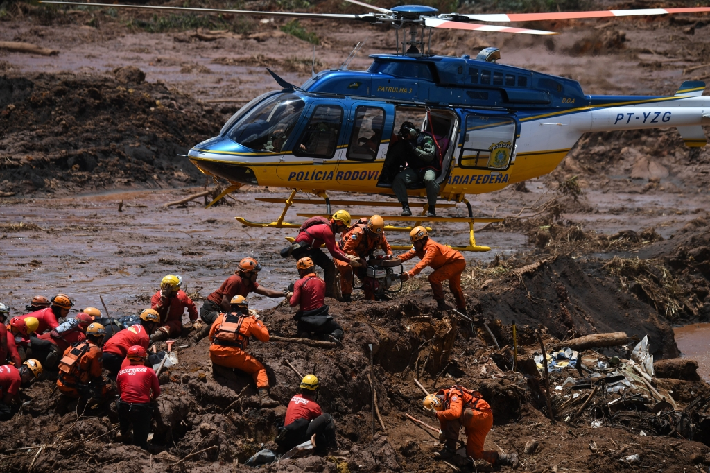 A helicopter provides support to the work of rescuers and firefighters in the search for victims, four days after the collapse of a dam at an iron-ore mine belonging to Brazil's giant mining company Vale near the town of Brumadinho, state of Minas Gerias, southeastern Brazil, on January 28, 2019. - The search for survivors intensified on Monday, on its fourth day, with the support of an Israeli contingent, after communities were devastated by a dam collapse that killed at least 60 people at a Brazilian mining complex -- with hopes fading for 292 still missing. A barrier at the site burst on Friday, spewing millions of tons of treacherous sludge and engulfing buildings, vehicles and roads. (Photo by Mauro Pimentel / AFP) (Photo credit should read MAURO PIMENTEL/AFP/Getty Images)