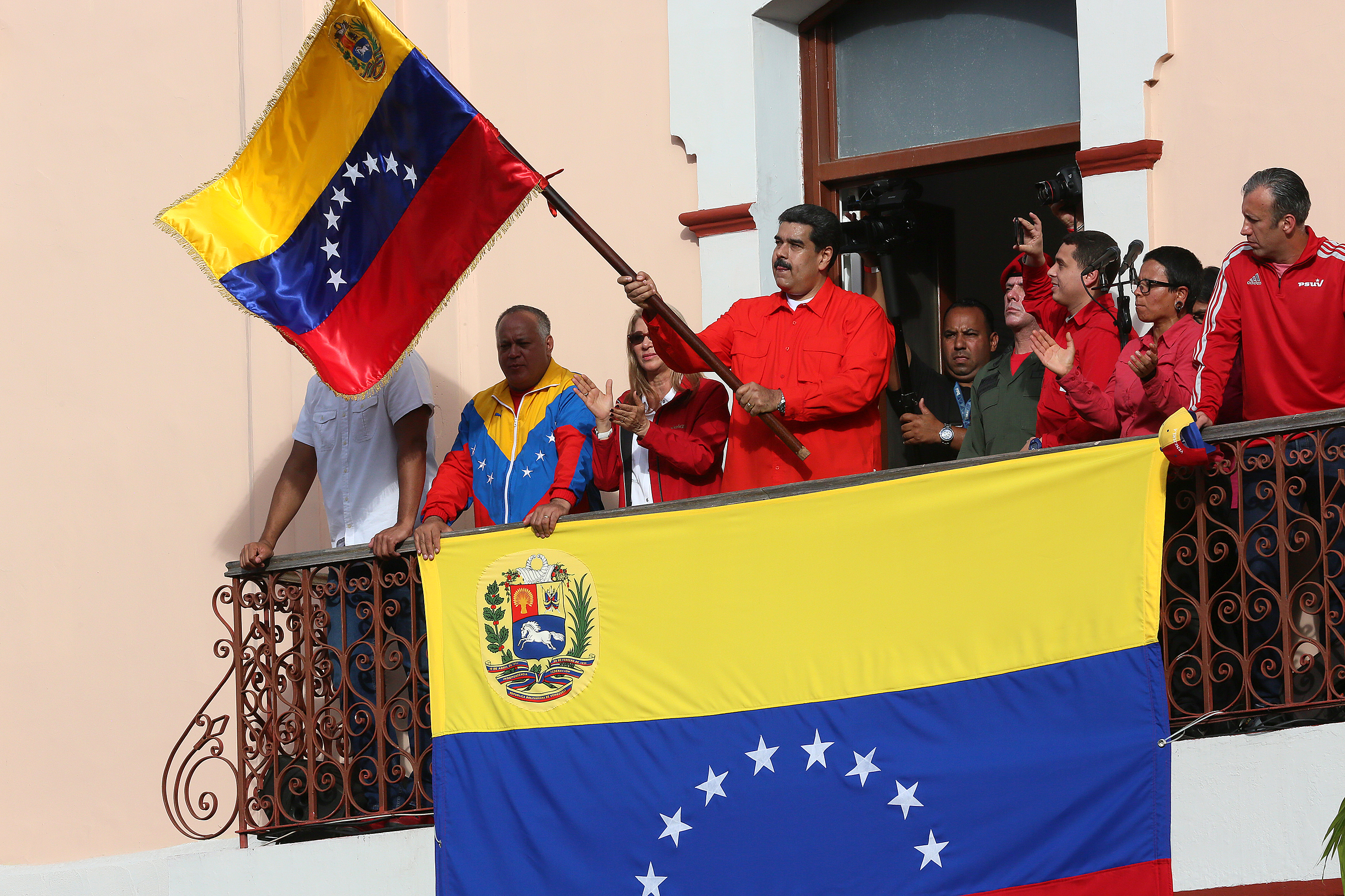 CARACAS, VENEZUELA - JANUARY 23: President of Venezuela Nicolás Maduro (C) waves a national flag as he is escorted by (FROM L TO R) Hector Rodriguez, Governor of Miranda; Diosdado Cabello, President of National Constitutional Assembly; Cilia Flores, First Lady; Major Erika Farias and Economic Vice President Tareck El Aissami at the Balcón del Pueblo of the Miraflores Government Palace on January 23, 2019 in Caracas, Venezuela. Earlier today, Venezuelan opposition leader and head of the National Assembly Juan Guaido declared self interim president as was officially accepted by presidents of many countries such as US, Brazil, Chile, Canada and Argentina. Head of Supreme Justice tribunal Juan Jose Mendoza urged general attorney to act against a constitution violation. Protests continue in Caracas. (Photo by Edilzon Gamez/Getty Images)
