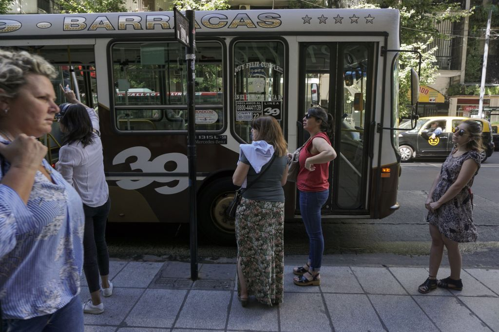 Commuters wait for a bus in Buenos Aires, on January 3, 2018. The Argentine government announced Wednesday 30% to 60% hikes in public transport fares in Buenos Aires, in its effort to reduce the fiscal deficit. / AFP PHOTO / EITAN ABRAMOVICH (Photo credit should read EITAN ABRAMOVICH/AFP/Getty Images)