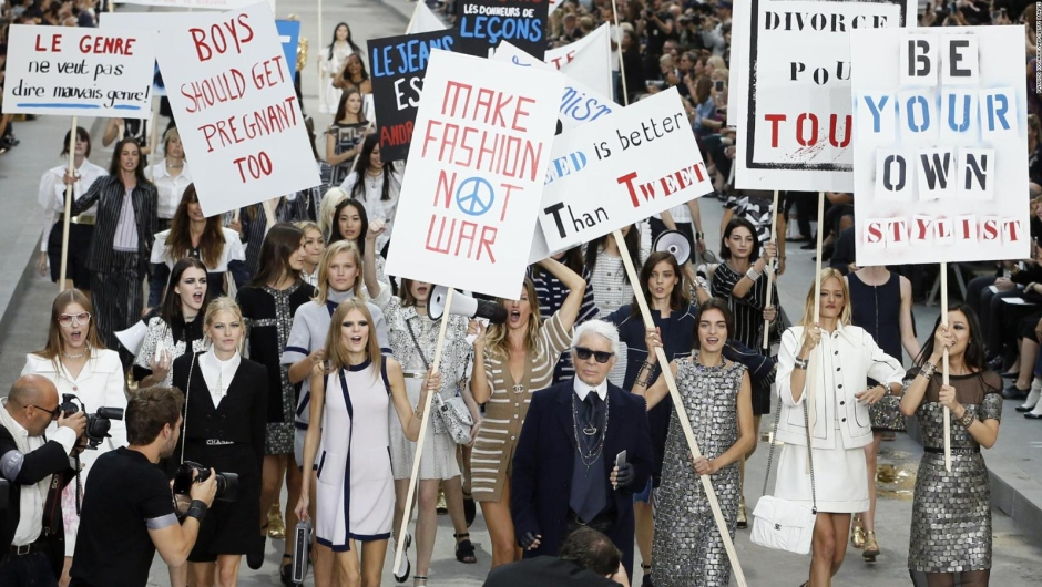 Lagerfeld, rodeado de modelos, camina por la pasarela después del desfile de Chanel Primavera-Verano 2015, con temática de protesta. Crédito: PATRICK KOVARIK/AFP/Getty Images