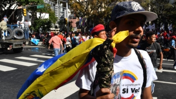 """A supporter of Venezuelan President Nicolas Maduro holds a figurine of late President Hugo Chavez as he arrives for a march of young leftists protesting """"imperialist intervention"""" -in reference to the aid convoys massing in Colombia which Maduro says is a """"political show"""" and a pretext for a US intervention, in the centre of Caracas on February 12, 2019. - The tug of war between the government and opposition is centred on whether humanitarian aid will be allowed into the economically crippled country, which suffers shortages of food, medicine and other basics. (Photo by Yuri CORTEZ / AFP) (Photo credit should read YURI CORTEZ/AFP/Getty Images)"""
