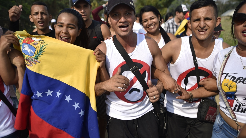 "People carry Venezuelan flags as they walk to the place where ""Venezuela Aid Live"" concert will be held at Tienditas International Bridge in Cucuta, Colombia, on February 22, 2019. - The concert was organized by British billionaire Richard Branson to raise money for the Venezuelan relief effort. Venezuela's political tug-of-war morphs into a battle of the bands on Friday, with dueling government and opposition pop concerts ahead of a weekend showdown over the entry of badly needed food and medical aid. (Photo by Luis ROBAYO / AFP) (Photo credit should read LUIS ROBAYO/AFP/Getty Images)"