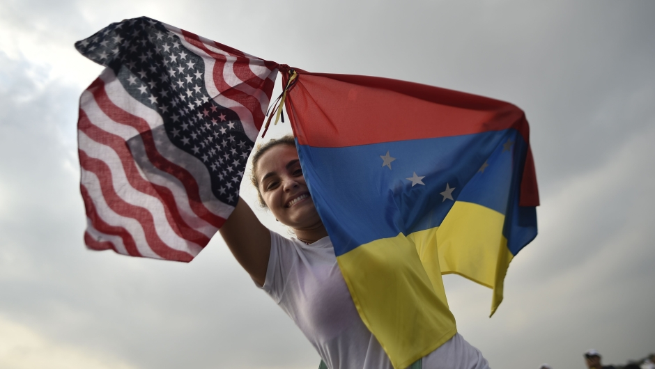 "A woman holds the Venezuelan and US flags as she waits for the start of ""Venezuela Aid Live"" concert, organized by British billionaire Richard Branson to raise money for the Venezuelan relief effort at Tienditas International Bridge in Cucuta, Colombia, on February 22, 2019 - The concert was organized by British billionaire Richard Branson to raise money for the Venezuelan relief effort. Venezuela's political tug-of-war morphs into a battle of the bands on Friday, with dueling government and opposition pop concerts ahead of a weekend showdown over the entry of badly needed food and medical aid. (Photo by Luis ROBAYO / AFP) (Photo credit should read LUIS ROBAYO/AFP/Getty Images)"