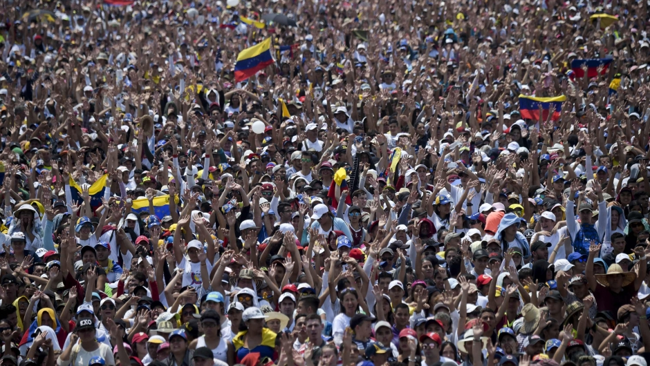 "People attend ""Venezuela Aid Live"" concert, organized to raise money for the Venezuelan relief effort at Tienditas International Bridge in Cucuta, Colombia, on February 22, 2019. - Venezuela's political tug-of-war morphs into a battle of the bands on Friday, with dueling government and opposition pop concerts ahead of a weekend showdown over the entry of badly needed food and medical aid. (Photo by RAUL ARBOLEDA / AFP) (Photo credit should read RAUL ARBOLEDA/AFP/Getty Images)"