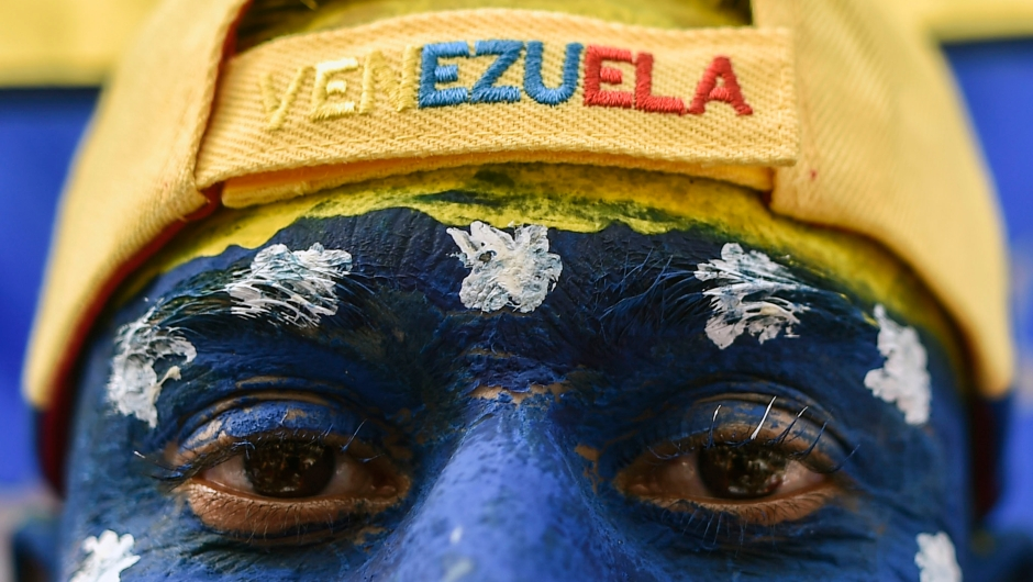 "A man with his face painted with Venezuela's national colours, attends the ""Venezuela Aid Live"" concert, organized to raise money for the Venezuelan relief effort at Tienditas International Bridge in Cucuta, Colombia, on February 22, 2019. - Thousands of people, many waving Venezuelan flags, streamed into a concert site on the Venezuela-Colombia border Friday for an international charity concert to push for humanitarian aid deliveries in defiance of a blockade by the government of President Nicolas Maduro. (Photo by Luis ROBAYO / AFP) (Photo credit should read LUIS ROBAYO/AFP/Getty Images)"